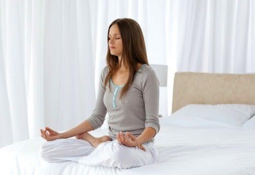 Femeie apelând la meditație pentru a alunga energia negativă din casă