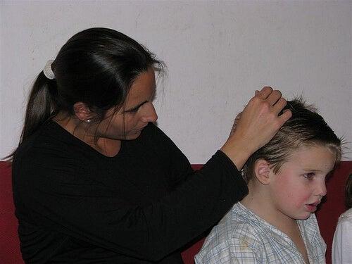Mamă curățând părul copilului de păduchi