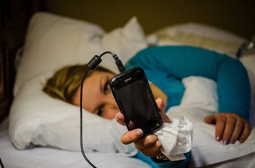 Femeie care ține în mână un telefon mobil