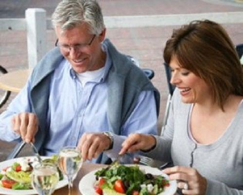 Cuplu trecut de 40 de ani servind o masă sănătoasă
