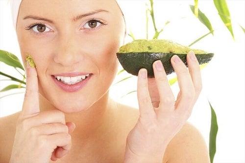 Femeie aplicând o mască de avocado