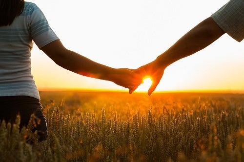 Cuplu ținându-se de mână la plimbare