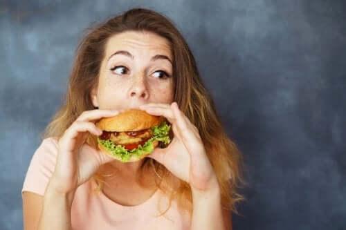 Femeie mâncând un hamburger