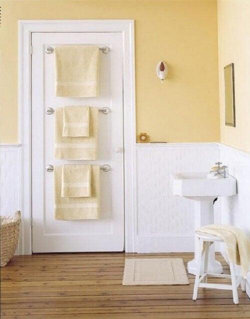 Pune un cuier sau suport pentru prosoape pe ușa din baie