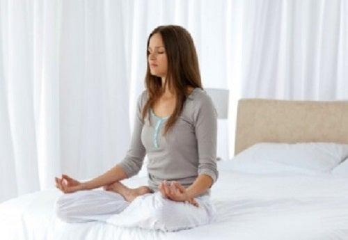 Femeie care meditează în dormitor