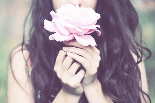 Femeie mirosind un trandafir