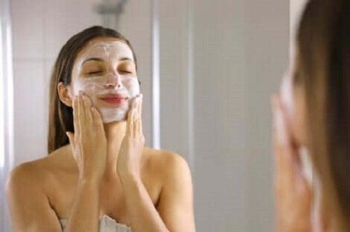 Femeie aplicând o mască pentru albirea tenului