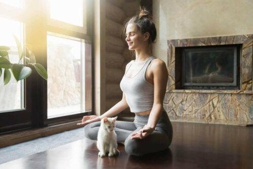 Femeie practicând meditație împreună cu pisica sa
