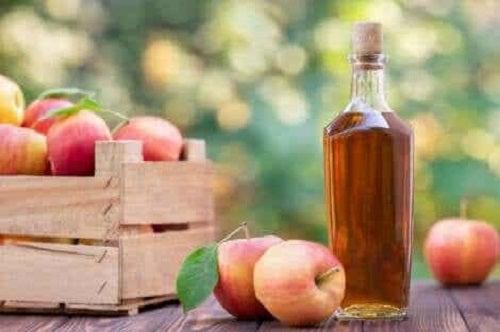 Sticlă cu oțet lângă o ladă cu mere