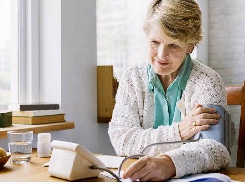 Bătrână care execută măsurarea corectă a tensiunii arteriale acasă