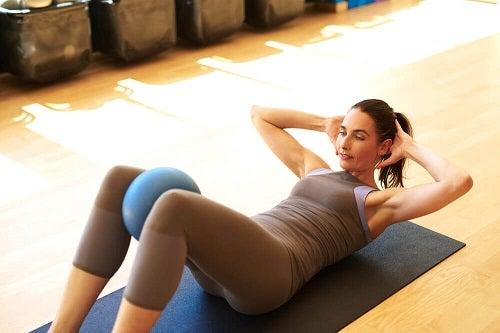 Exerciții pentru un abdomen plat precum ridicarea genunchilor