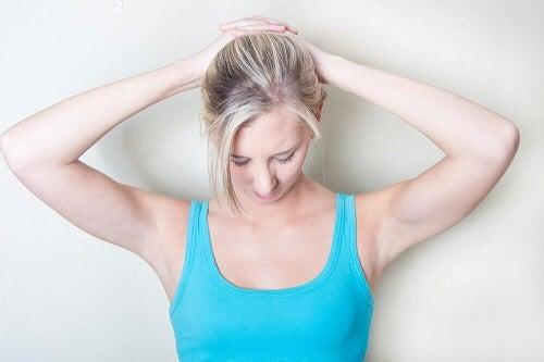 Femeie practicând exerciții pentru reducerea durerii cervicale