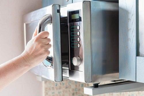 Gospodină încercând o prăjitură preparată la cuptorul cu microunde