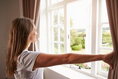 Femeie care aplică sfaturi pentru eliminarea energiilor negative din casă