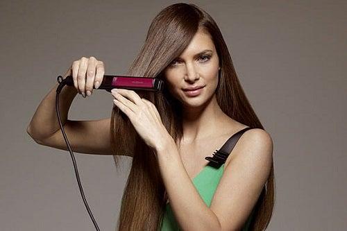 Femeie care folosește o placă de păr