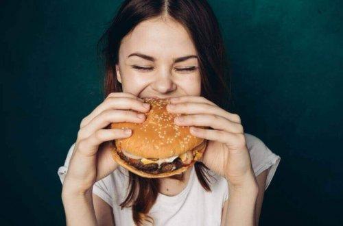 Femeie care mănâncă fast food