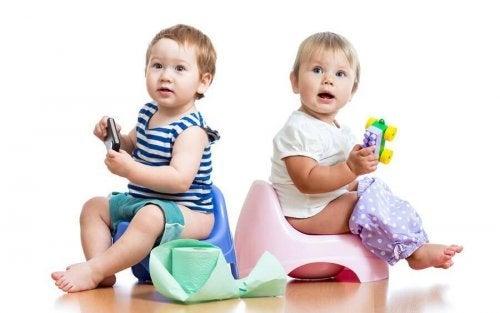 Bebeluși care exersează învățatul la oliță