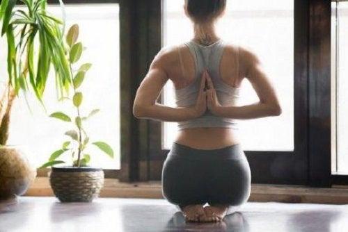 Poziție de yoga cu mâinile la spate