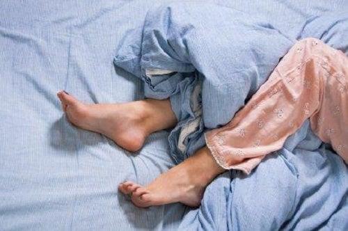 Femeie care suferă de sindromul picioarelor neliniștite
