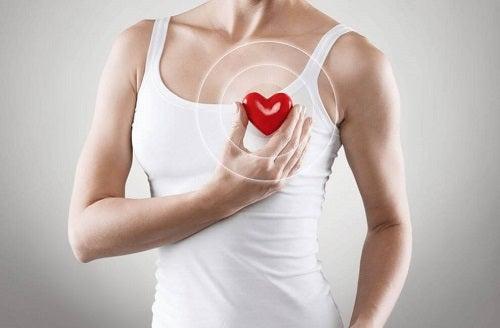 Femeie care ține în mână o inimă roșie