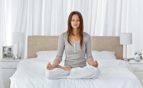 Femeie care meditează în pat