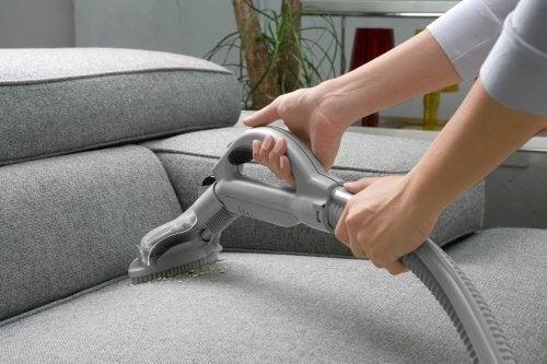 Persoană care aspiră canapeaua
