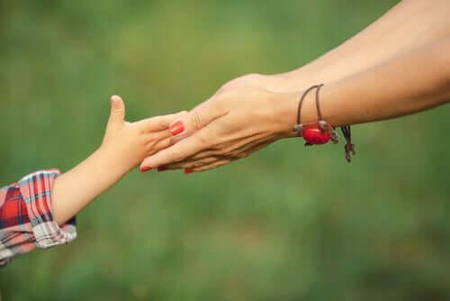 Copil și adult ținându-se de mână
