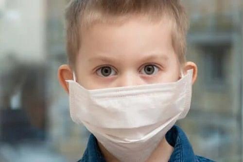 Copil care poartă mască pentru coronavirus