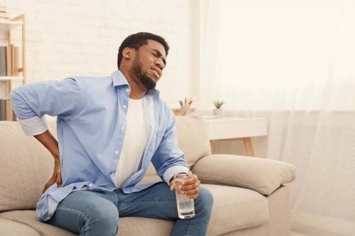 Bărbat cu dureri ținând un pahar de apă în mână