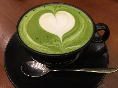 Cană de ceai verde cu spumă în formă de inimă