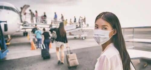 Femeie care urcă în avion cu mască de protecție