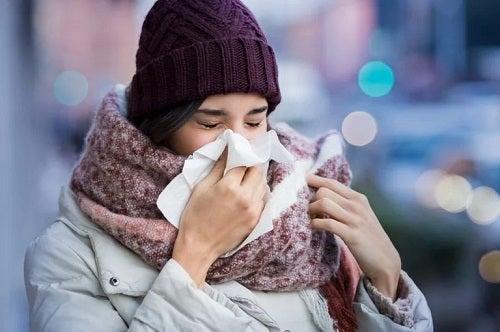 Femeie care își suflă nasul pe stradă
