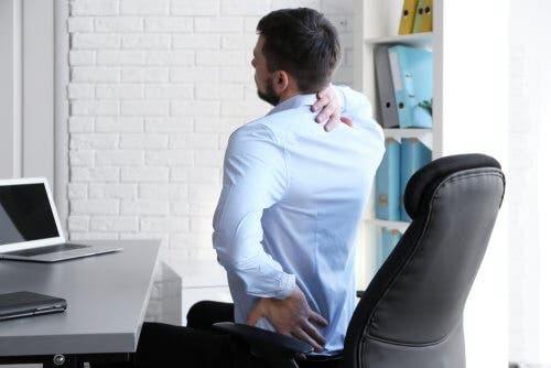 Bărbat adoptând obiceiuri care ameliorează durerea lombară la birou