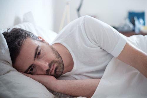 Bărbat supărat stând în pat