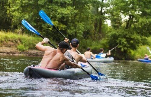 Bărbați vâslind cu barca pe râu