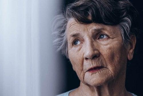 Bătrână uitându-se pe fereastră