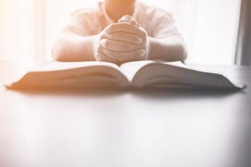 Copil citind o carte de rugăciuni