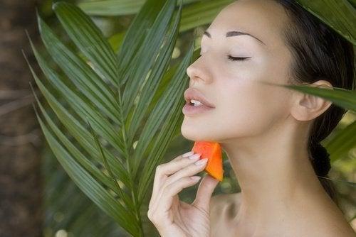 Femeie profitând de principalele beneficii pentru piele ale fructului de papaya