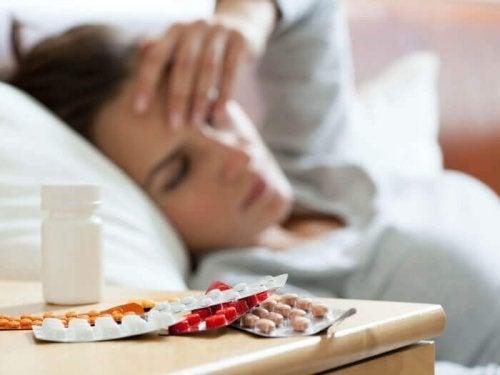 Femeie bolnavă cu medicamente pe noptieră