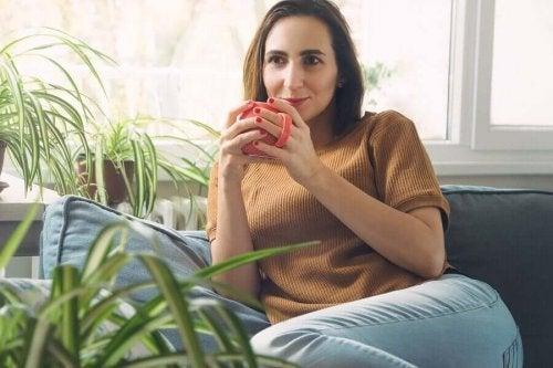 Femeie care profită de reducerea timpului pe mobil bând cafea