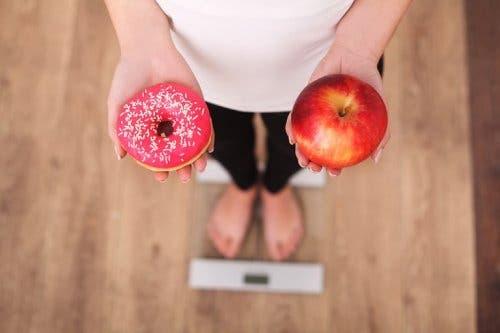 Femeie stând pe un cântar și ținând în mână o gogoașă și un măr