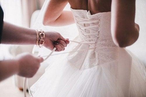 Femeie legând corsetul miresei