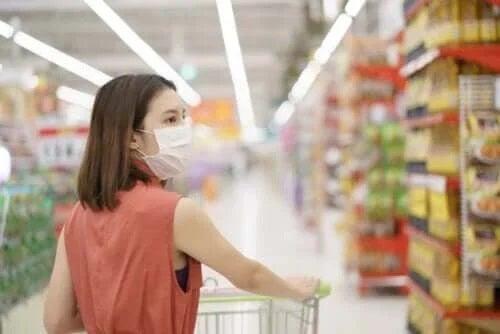 Femeie care face cumpărături purtând o mască