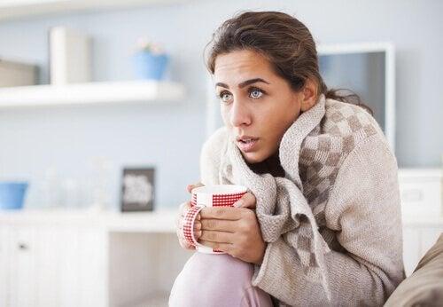 Femeie cu frisoane bând o băutură caldă
