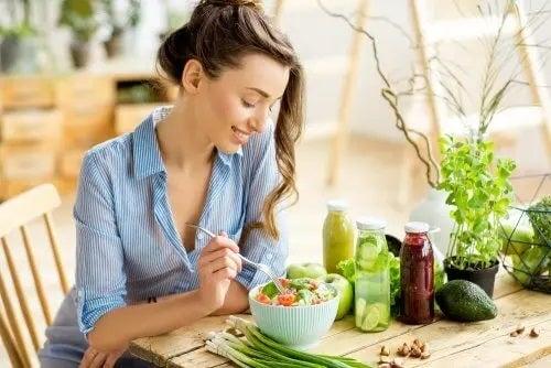 Femeie care consumă legume la masă