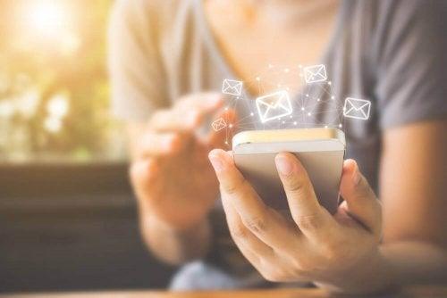 Femeie verificând mesajele de email pe telefonul mobil