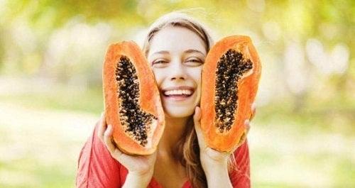Femeie pozând cu un papaya tăiat în două
