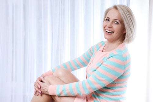 Femeie cu părul grizonat îmbrățișând schimbările care survin la menopauză