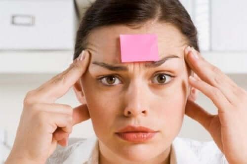 Femeie cu hârtie lipită de frunte experimentând simptomele amneziei