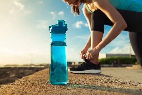 Sportivă antrenându-se cu o sticlă de apă